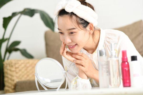 鏡を見てスキンケアする女性