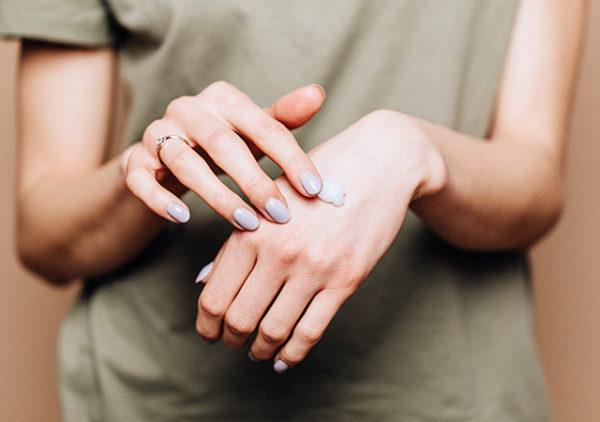 手の甲でクリームを伸ばす女性